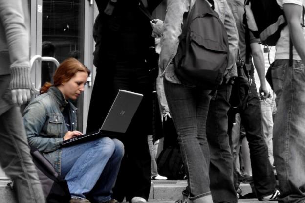 Frau mit Laptop in Menschenmenge